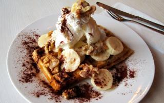 Vegan waffle with banana, cream and caramel sauce