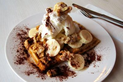 Vegan waffle with banana, cream and caramel sauce